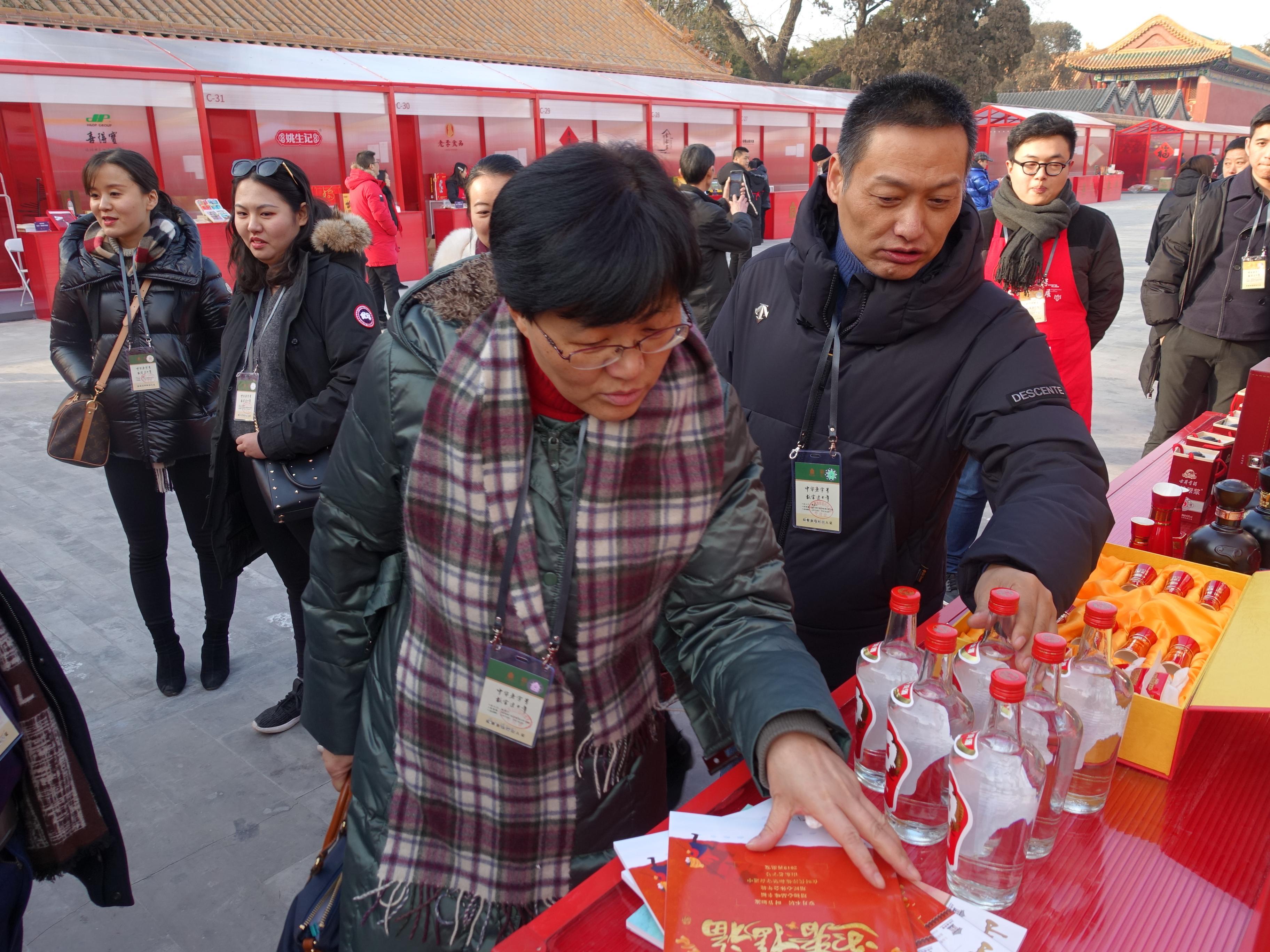 安徽省商务厅流通处处长张远琴(前排左一)与省老字号企业协会会长胡明朗(前排左二)关注古井贡酒
